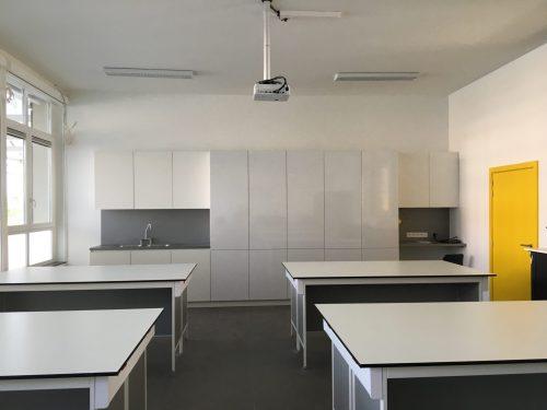 Inbouwkast en bureau's in klas met projectievlak voor beamer